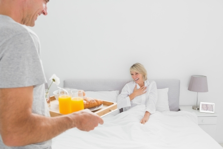 Man bringing breakfast in bed to his partner at home in bedroom photo