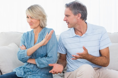 Man pleading with his wife after a fight at home on the couch Stock Photo