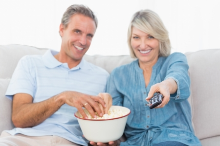 changing channel: Couple watching tv and eating popcorn on the couch at home in living room