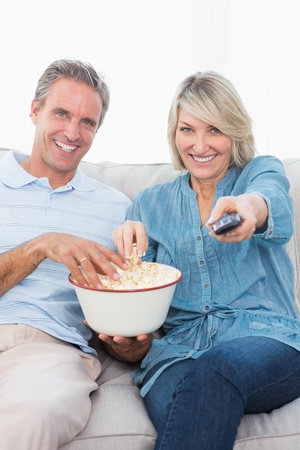 changing channel: Couple watching tv and eating popcorn on the sofa at home in living room