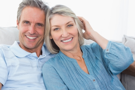 Smiling couple on their couch looking at camera Stock Photo - 20628142