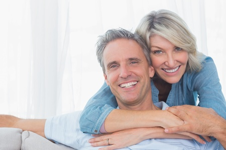 hugging couple: Couple smiling at the camera at home in living room