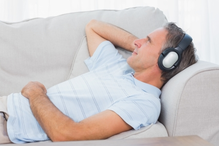 Man lying on couch listening to music at home in living room photo