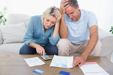 Worried couple going over finances at home in living room photo