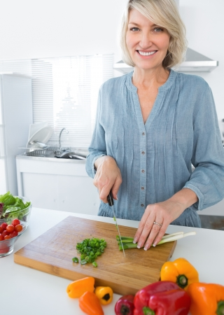 Cheerful woman chopping vegetables at the kitchen counter photo