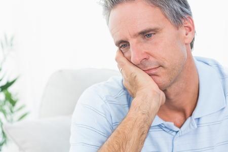 hombre pensando: Hombre deprimido pensando en su casa en el sofá