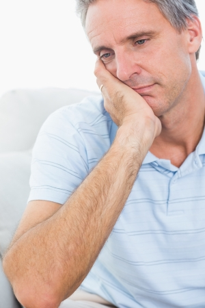 Upset man thinking at home on couch photo