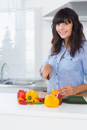 Pretty brunette slicing pepper at kitchen counter photo
