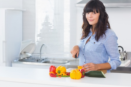 Pretty brunette cutting pepper at kitchen counter photo