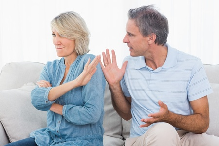 pleading: Man pleading with his wife after an argument at home on couch