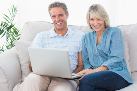 Happy couple using laptop together on the couch looking at camera at home in living room photo