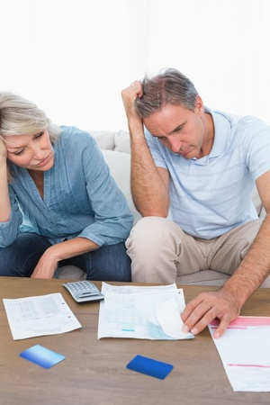 Anxious couple going over bills at home in living room photo