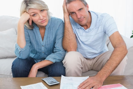 Anxious couple going over bills looking at camera at home in living room Stock Photo - 20630888