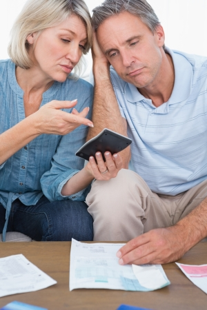 figuring: Anxious couple going over their debt at home in living room