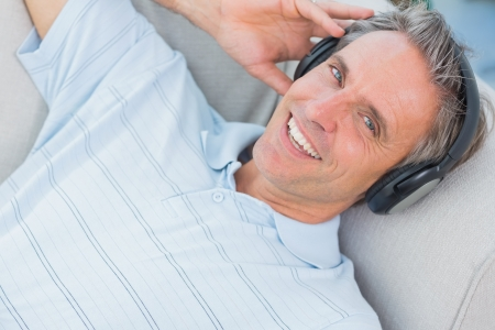 Man lying on sofa listening to music smiling at camera at home photo