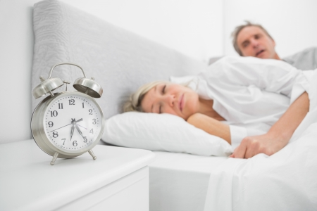 early 40s: Man looking at ringing alarm clock as his wife is still asleep