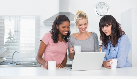 Smiling friends having coffee together and looking at laptop at home in kitchen Stock Photo - 20625930