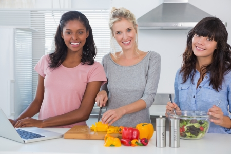 Cheerful friends making salad and using laptop for recipe looking at camera at home in kitchen Stock Photo - 20626846
