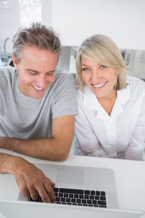Smiling couple using their laptop in the morning sitting at kitchen counter photo