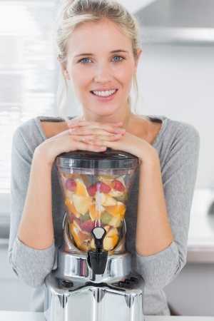Blonde woman leaning on her juicer full of fruit and smiling at camera at home in kitchen photo