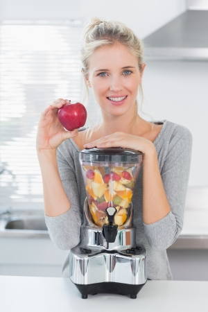 Pretty woman leaning on her juicer full of fruit and holding red apple at home in kitchen photo