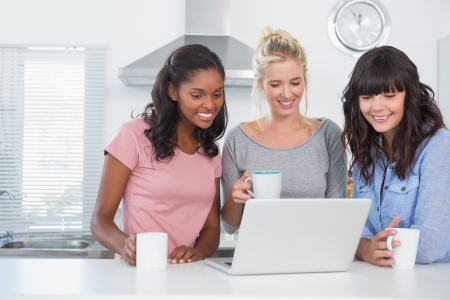 Pretty friends having coffee together and looking at laptop at home in kitchen Stock Photo - 20626697