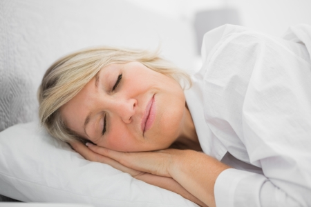 peacefully: Blonde woman sleeping peacefully at home in bed Stock Photo