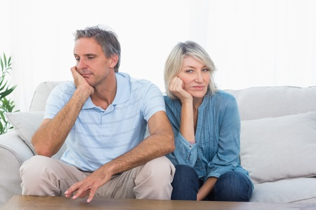 people arguing: Couple not speaking after a fight at home on couch Stock Photo