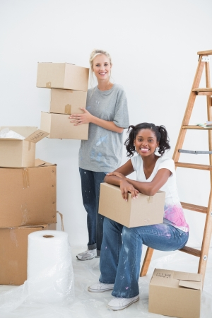 Cheerful housemates carrying cardboard moving boxes and smiling at camera in new home photo