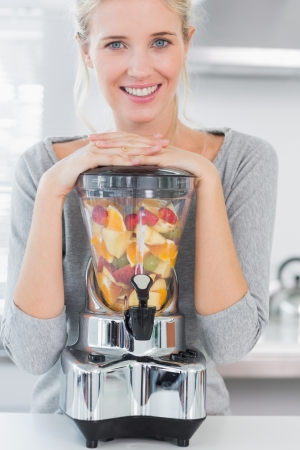 Blonde woman leaning on her juicer full of fruit at home in kitchen photo