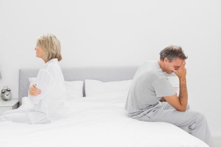 Couple sitting on opposite sides of bed after a dispute photo