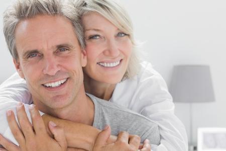 embracing couple: Cari�osa pareja sonriendo a la c�mara en casa en el dormitorio