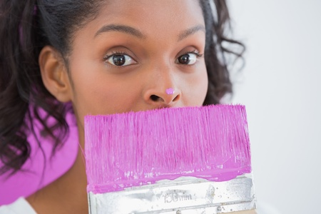 redecorating: Pretty woman holding paintbrush with pink paint on her nose looking at camera
