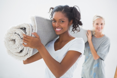 roommates: Happy housemates carrying rolled up rug looking at camera in new home