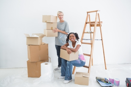 relocating: Smiling housemates carrying cardboard moving boxes and looking at camera in new home Stock Photo