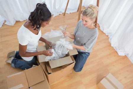unwrapping: Young housemates unpacking boxes in new home and chatting together