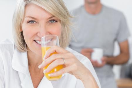 Happy woman drinking orange juice in kitchen with partner standing behind photo