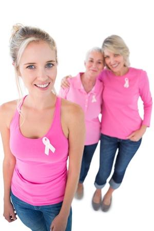cancer de mama: Tres mujeres vistieron camisas de color rosa y cintas de c�ncer de mama en el fondo blanco