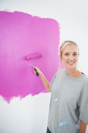 Happy blonde painting her wall pink and smiling at camera in new home photo