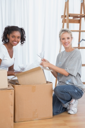 unwrapping: Cheerful friends unpacking boxes in new home and smiling at camera