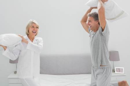 Laughing couple having a pillow fight at home on bed photo