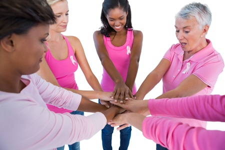 Women wearing pink and ribbons for breast cancer putting hands together on white background photo
