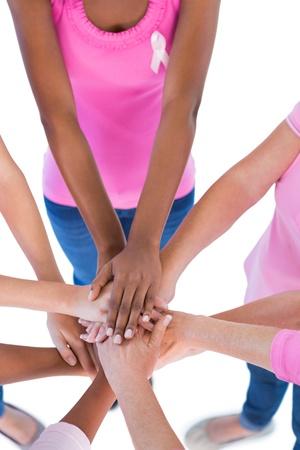 cancer de mama: Grupo vestida de rosa y cintas para el c�ncer de mama poniendo las manos en el fondo blanco Foto de archivo