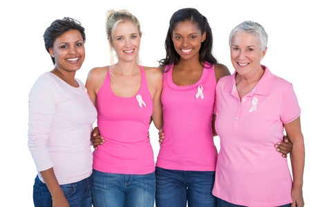 Glimlachende vrouwen die roze topjes en borstkanker linten op witte achtergrond Stockfoto