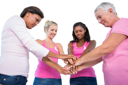 Smiling women wearing breast cancer ribbons putting hands together on white background photo