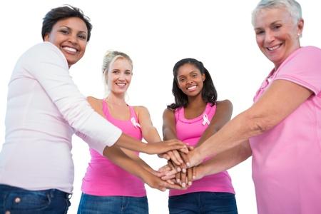 cancer de mama: Sonriente mujer usando cintas de c�ncer de mama que ponen las manos juntas sonriendo a la c�mara sobre fondo blanco Foto de archivo