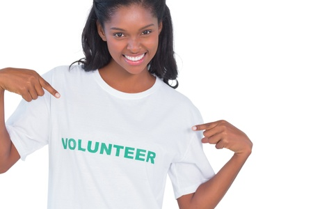 volunteer point: Smiling young woman wearing volunteer tshirt and pointing to it on white background