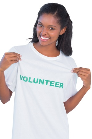 altruismo: Mujer joven con camiseta de voluntario y apuntando a ella en el fondo blanco Foto de archivo