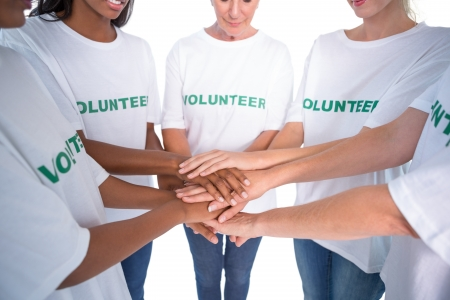 Group of female volunteers with hands together on white background Stock Photo