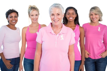 Diverse group of women wearing pink tops and breast cancer ribbons on white background photo